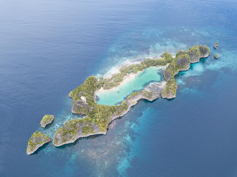 Aerial View of Amazing Tropical Islands in Raja Ampat. A beautiful set of limestone islands is surrounded by a healthy coral reef in Raja Ampat, Indonesia. This royalty free stock photography