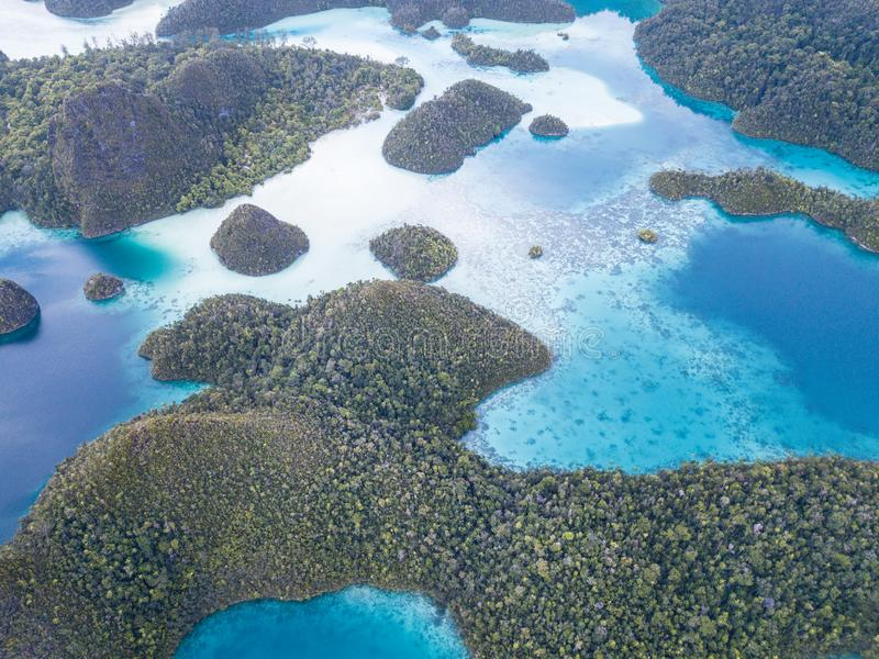 Aerial View of Amazing Tropical Islands in Raja Ampat. Limestone islands rise from a gorgeous lagoon in Wayag, Raja Ampat, Indonesia. This remote, tropical stock photo