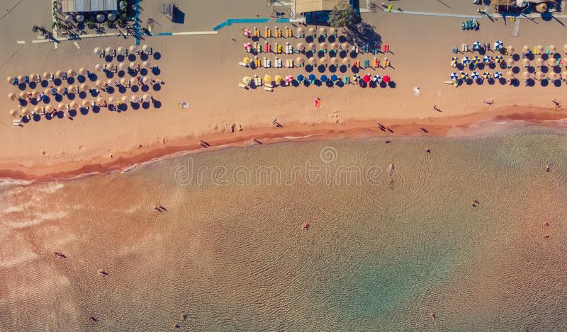 Aerial view of amazing turquoise sea with white umbrellas and sun loungers. people are walking on shore. Beautiful sunny stock photos