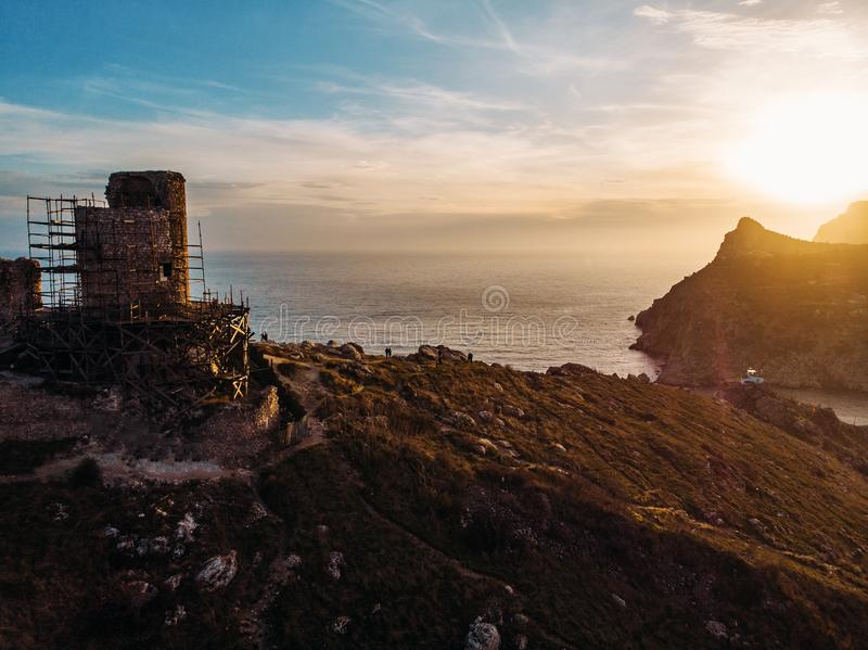 Aerial view of ancient ruined Cembalo fortress on cliff of Balaklava mountains at sunset, beautiful nature landscape with sea stock photos