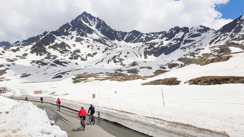 An aerial view of an attractive group of people riding bikes on a road in the mountain view with snow in Dolomite Mountains stock images
