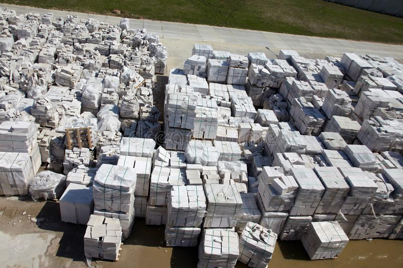 Aerial view of autoclaved aerated concrete blocks, both defective and good, on pallets, stored at factory warehouse.  stock images