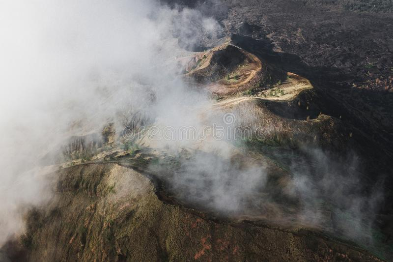 Aerial drone view of Batur volcano caldera in Bali. Aerial view of Batur volcano caldera in Bali. Volcanic black texture and crater rim, view from above, drone stock photography