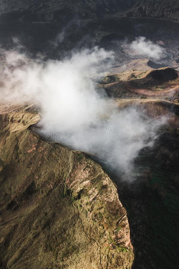 Aerial drone view of Batur volcano caldera in Bali. Aerial view of Batur volcano caldera in Bali. Volcanic black texture and crater rim, view from above, drone royalty free stock images