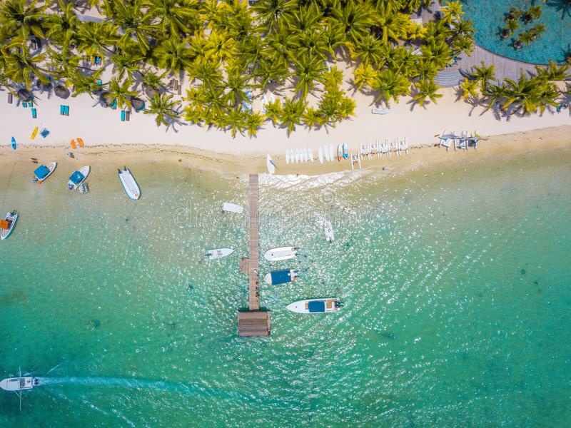 Aerial view on beautiful beach in Trou aux Biches, Mauritius. View of the footbridge and green palms, boats and white sand beach stock photo