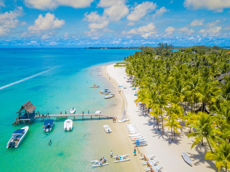Aerial view on beautiful beach in Trou aux Biches, Mauritius. View of the footbridge and green palms, boats and white sand beach stock photography