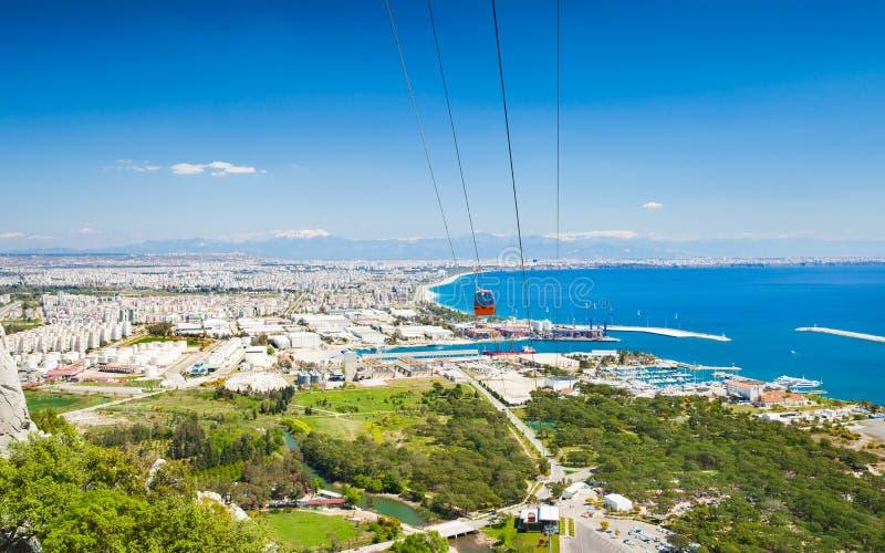 Aerial view of beautiful blue Gulf of Antalya and popular seaside resort city Antalya, Turkey. Tunektepe Cable Car is aerial lift serving peak of Tunek Tepe stock photo