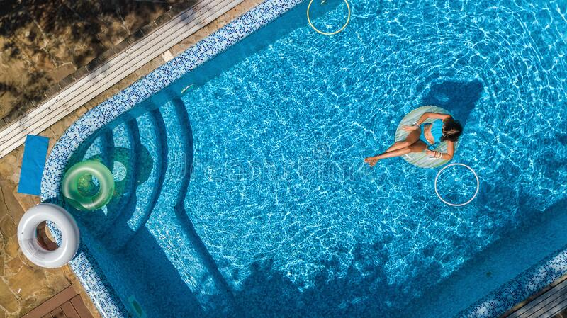 Aerial view of beautiful girl in swimming pool from above, swim on inflatable ring donut and has fun in water on family vacation royalty free stock images