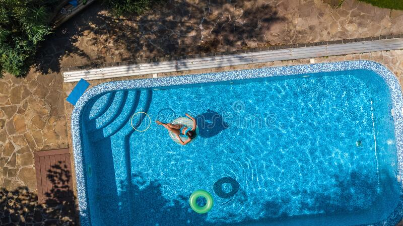 Aerial view of beautiful girl in swimming pool from above, swim on inflatable ring donut and has fun in water on family vacation stock images