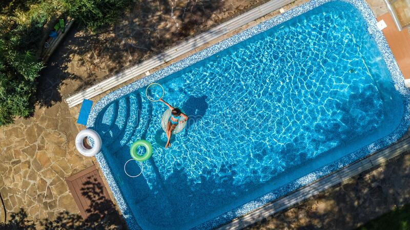 Aerial view of beautiful girl in swimming pool from above, swim on inflatable ring donut and has fun in water on family vacation royalty free stock photography