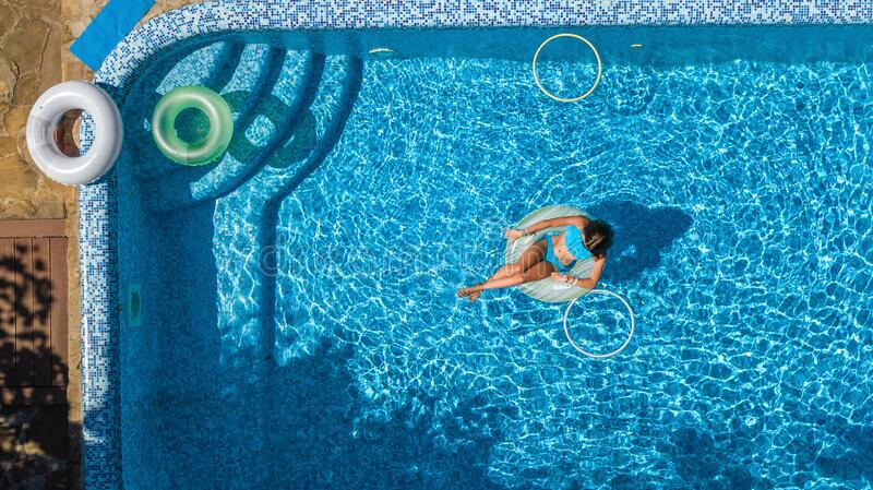 Aerial view of beautiful girl in swimming pool from above, swim on inflatable ring donut and has fun in water on family vacation stock photography