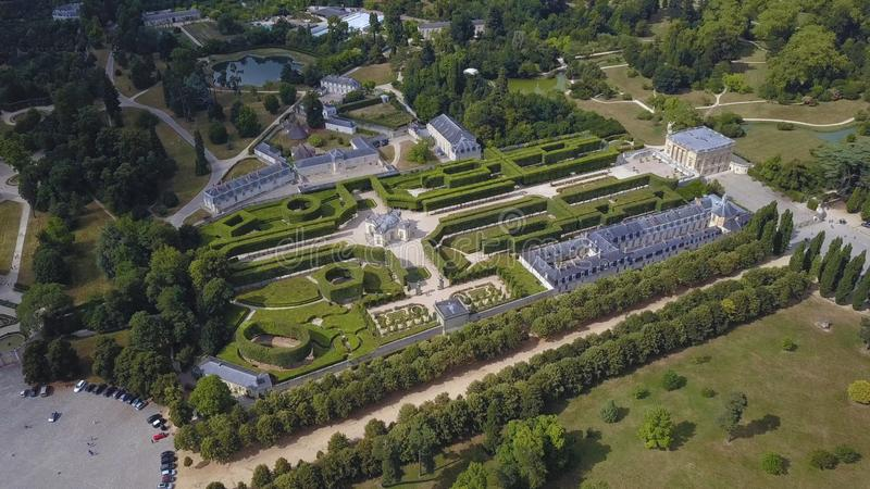 Aerial view of beautiful light palace and other buildings in architectural complex with picturesque French garden. Surrounded by green forest. Historical stock photo