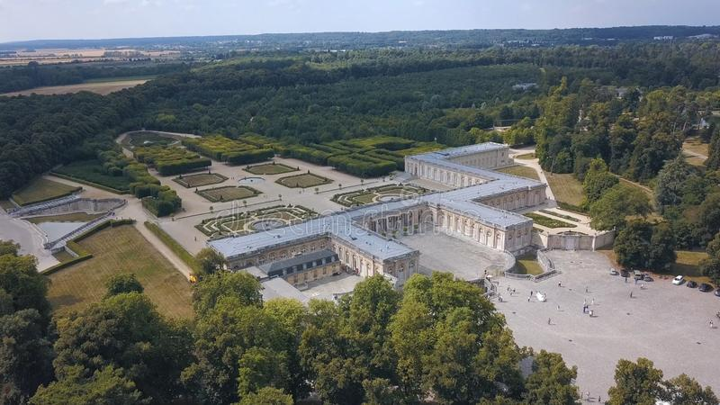 Aerial view of beautiful light palace with square and picturesque French garden surrounded by green forest against blue. Sky. Historical buildings royalty free stock photos