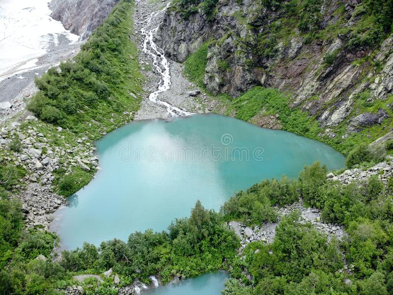 An aerial view of the beautiful mountain lake with turquoise water surrounded by forest and rocks. Panorama from drone stock image