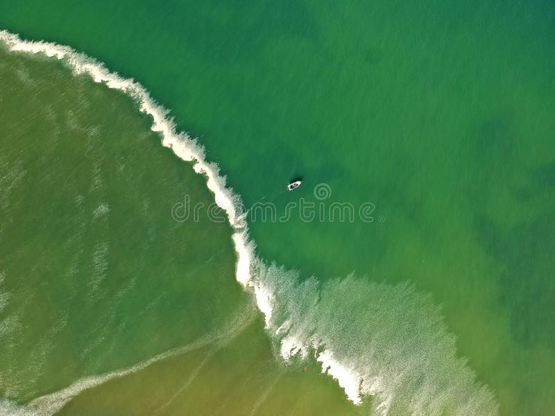 Aerial view at beautiful sea with small fishing boat in the center. royalty free stock image