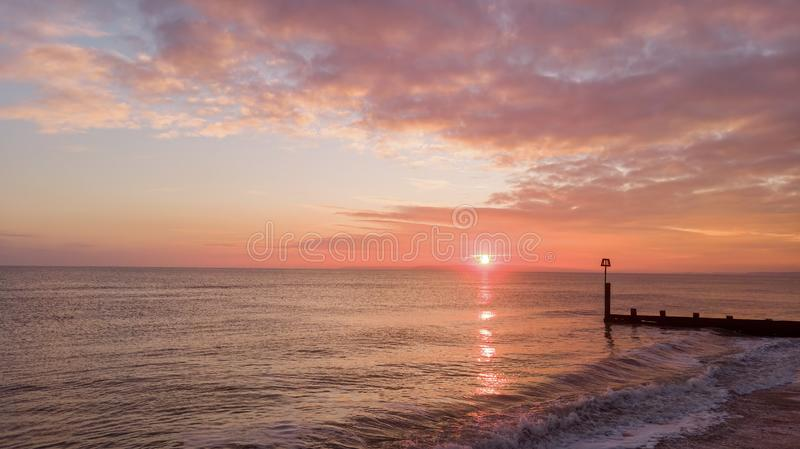 An aerial view of a beautiful sunset with orange circle sun and reflection on a calm sea along a sandy beach and groyne stock photos