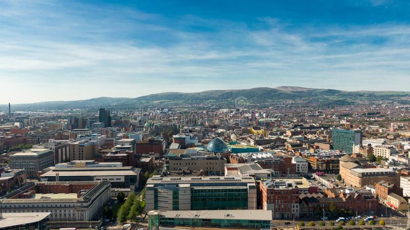 Aerial view of Belfast  in Northern Ireland at Night. Sunset above City, mountains or hills on backgroundFootpath between trees in stock photography