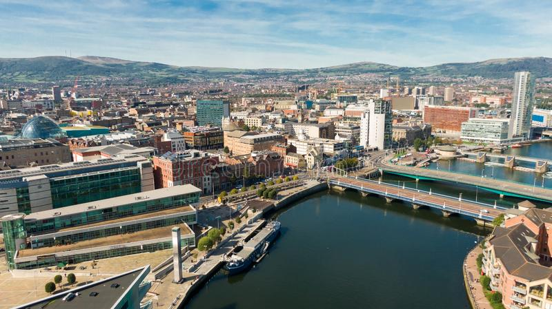 Aerial view of Belfast  in Northern Ireland at Night. Sunset above City, mountains or hills on backgroundFootpath between trees in royalty free stock image
