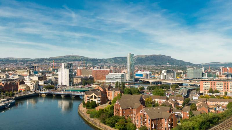 Aerial view of Belfast  in Northern Ireland at Night. Sunset above City, mountains or hills on backgroundFootpath between trees in stock photo