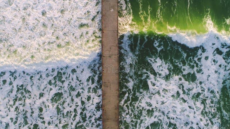 Aerial view of big sea waves and old broken bridge stock photo