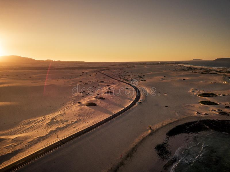 Aerial view of black asphalt road in the middle of desert and beach - concept of travel in beautiful scenic place and vacation stock photo