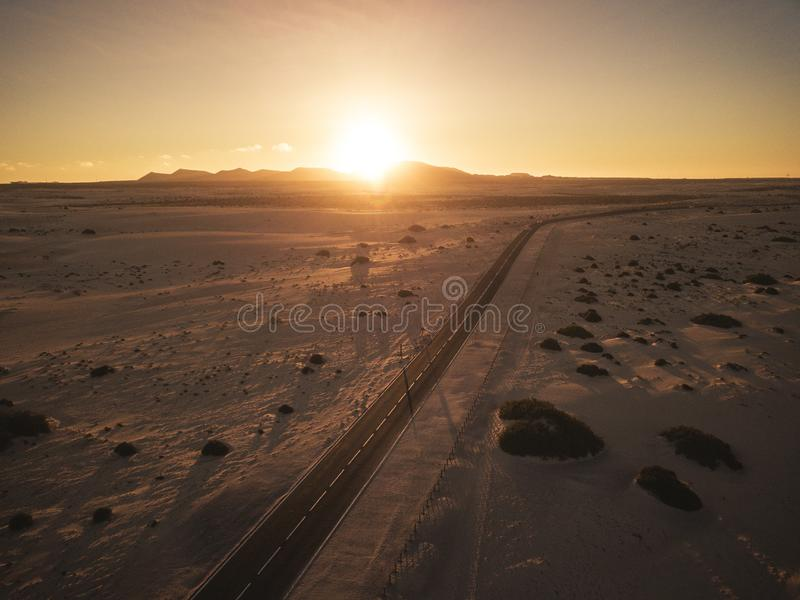 Aerial view of black asphalt straight road in the middle of desert and mountains - concept of travel in beautiful scenic place and. Vacation with car sunset in royalty free stock photo