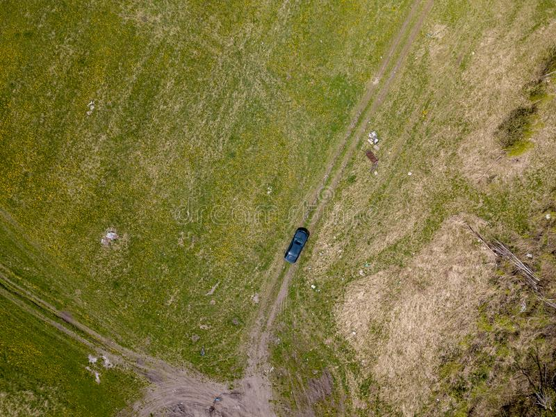 Aerial view of a black car standing in a field in the middle of green grass on a country road on a clear spring day. Travel by. Vehicle and solitude with nature stock image