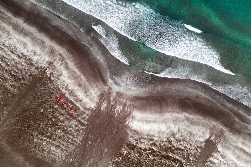 Aerial view of black sand beach and ocean waves. Red kayaks ready for swimming stock images