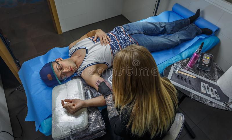 Aerial view of a blonde girl accurately tattooing the  arm of a boy in her tattoo studio. Aerial view of a blonde girl accurately tattooing the  arm of a boy in stock images