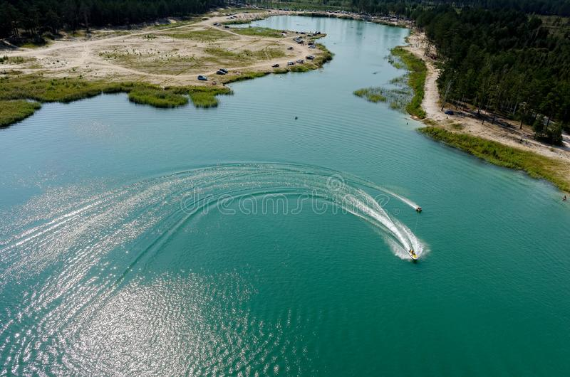 Aerial view of Blue Lake beach in Tyumen. Russia. Aerial view onto beach on so-calles Blue Lake and hydrocycle tows the inflatable watercraft circle. Tyumen stock photo