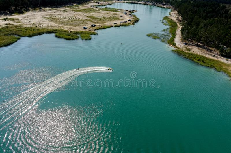 Aerial view of Blue Lake beach in Tyumen. Russia. Aerial view onto beach on so-calles Blue Lake and hydrocycle tows the inflatable watercraft circle. Tyumen stock images