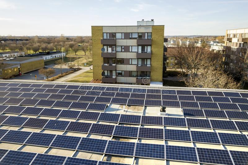 Aerial view of blue shiny solar photo voltaic panels system on commercial roof producing renewable clean energy on city landscape. Background stock photography