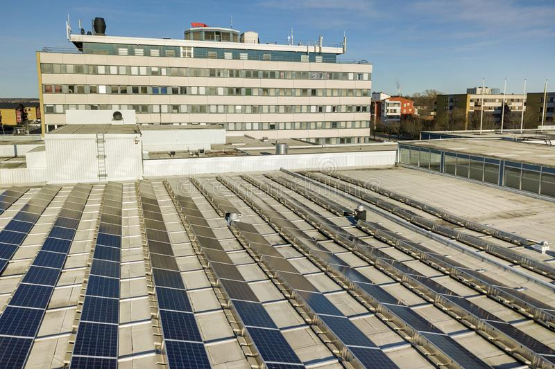 Aerial view of blue shiny solar photo voltaic panels system on commercial roof producing renewable clean energy on city landscape royalty free stock images