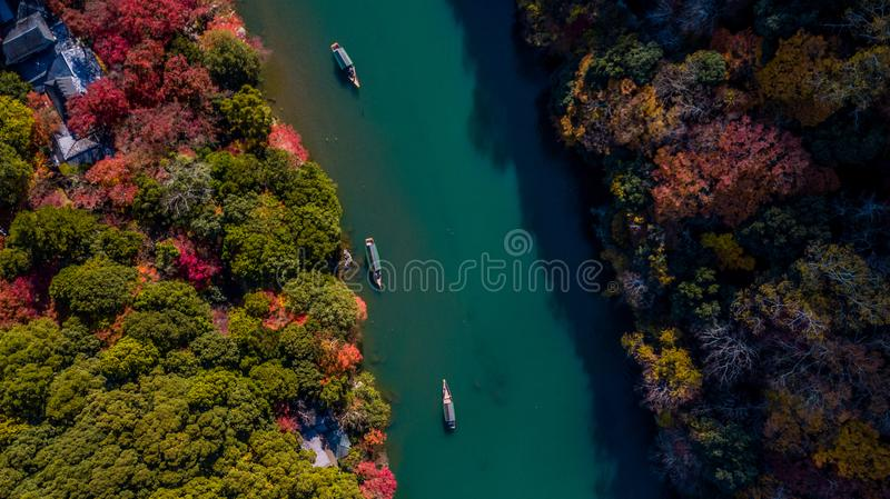 Aerial view Boatman punting the boat for tourists to enjoy the f. All color season view of Hozu river in Togetsukyo bridge is one of the most scenic Arashiyama stock images