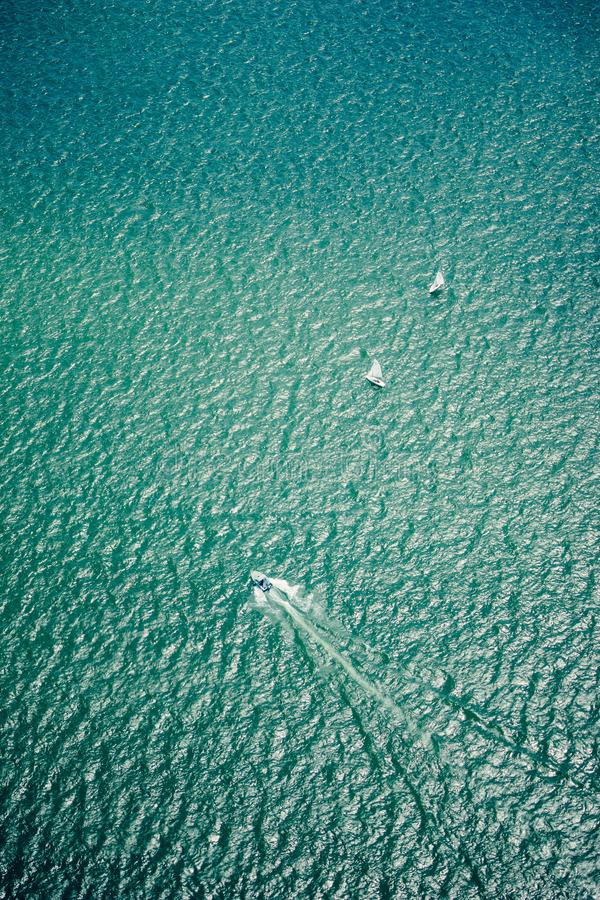 Boats sailing on rippling water as seen from the air stock image