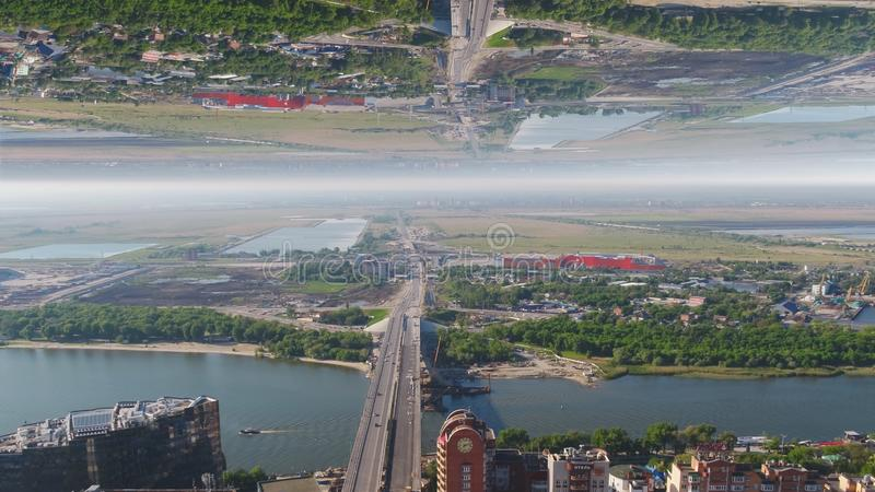 Aerial view of the bridge crossing wide river near a city, mirror horizon effect. Media. Summer landscape with green stock photo
