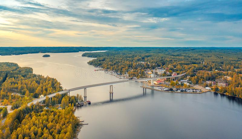 Aerial view on the bridge over the lake and trees in the forest on the shore. Blue lakes, islands and autumn forests from above on royalty free stock photography