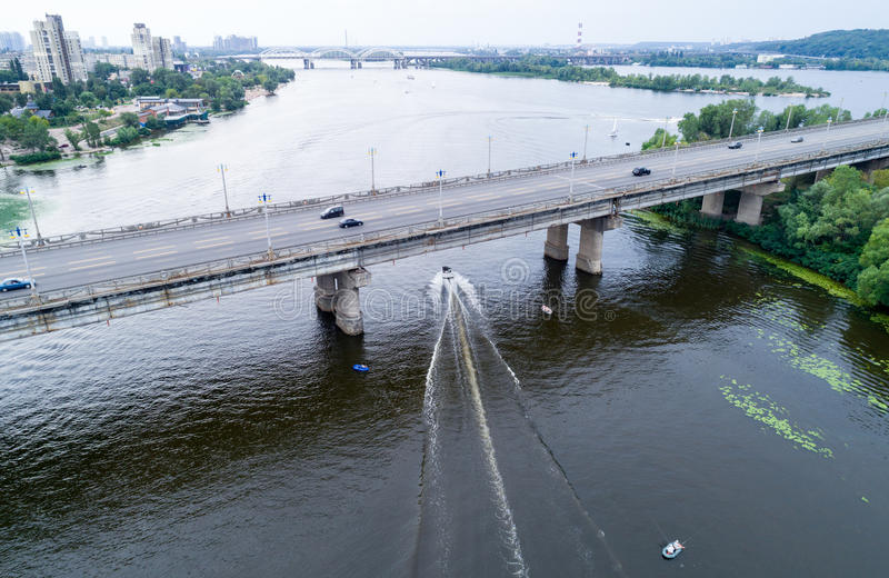 Aerial view of the bridge and the road over the Dnepr River over a green island in the middle of the river. With boats. Kiev, Ukraine stock image