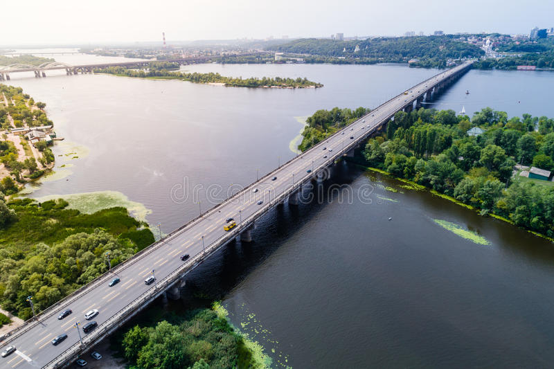 Aerial view of the bridge and the road over the Dnepr River over a green island in the middle of the river. Kiev, Ukraine stock photo