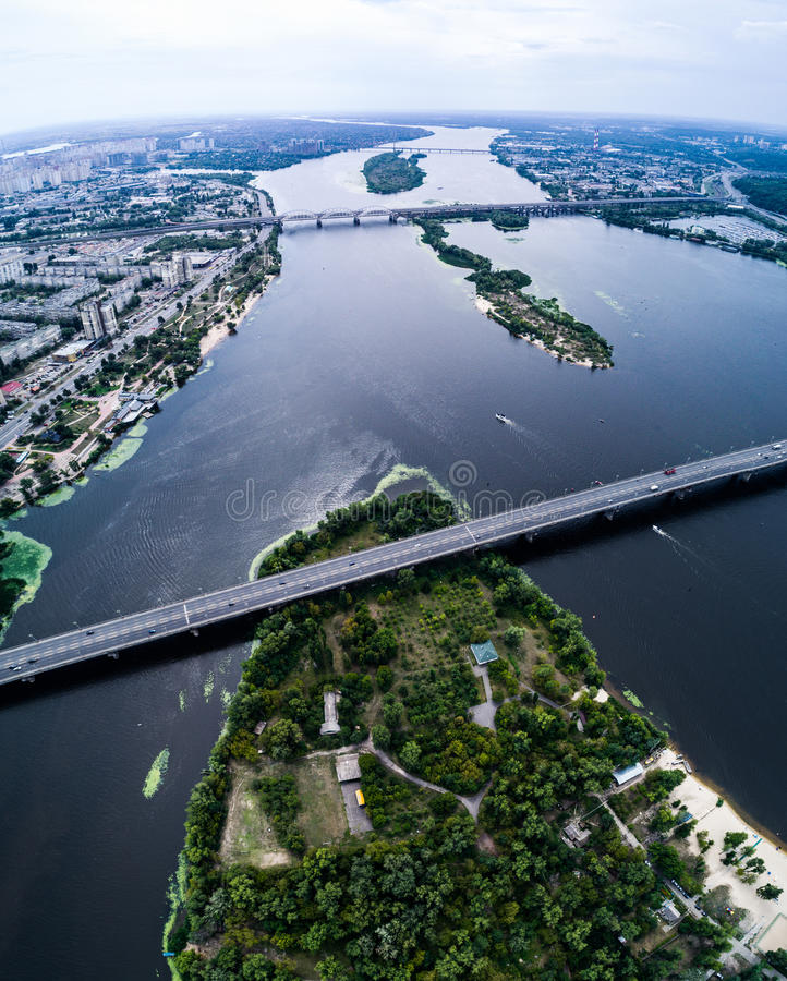 Aerial view of the bridge and the road over the Dnepr River over a green island in the middle of the river. Kiev, Ukraine royalty free stock photos