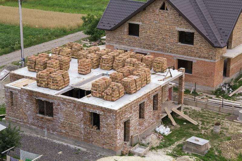 Aerial view of building site in green field. Brick basement floor of future cottage and not finished new big brick house with bro. Wn shingled roof. Construction stock image