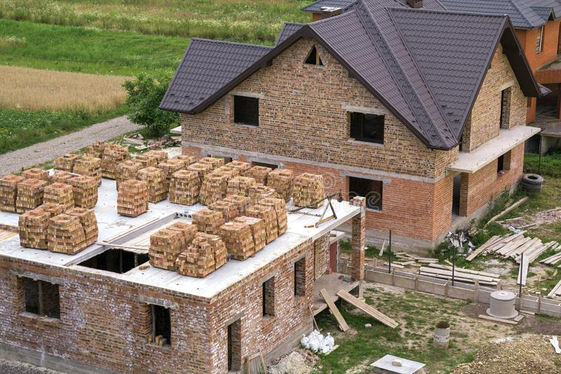 Aerial view of building site in green field. Brick basement floor of future cottage and not finished new big brick house with brow. N shingled roof. Construction royalty free stock photos