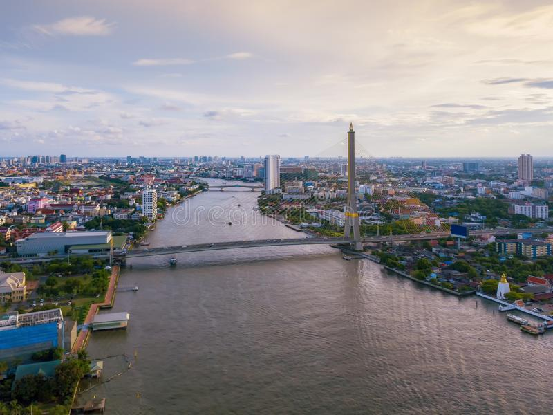 Aerial view of buildings with Chao Phraya River in transportation concept. Bangkok skyline background, Urban city in downtown area. At sunset, Thailand stock image