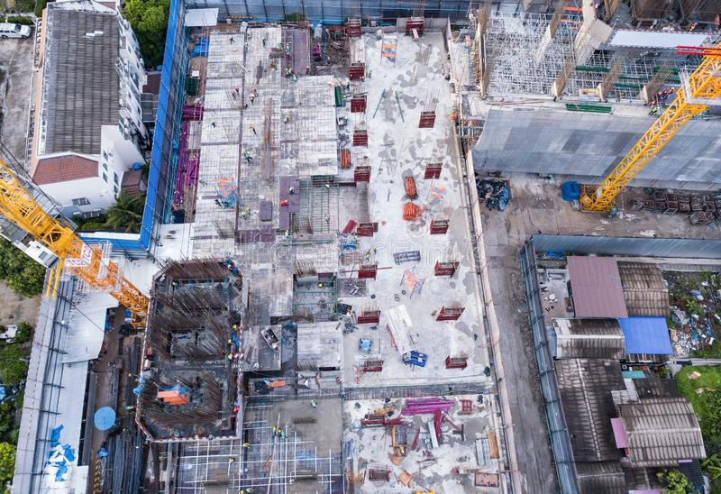 Aerial view of busy industrial construction site workers with cranes working. Top view of development high rise architecture. Building at noon stock photo