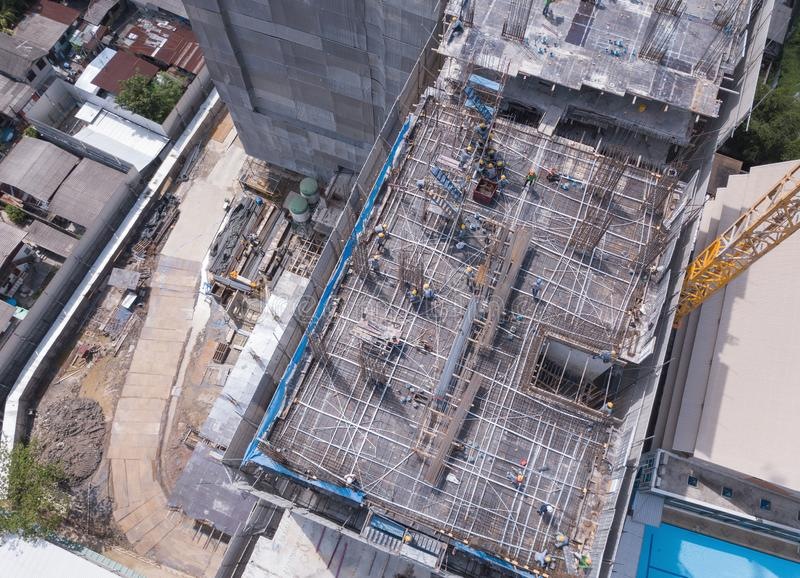 Aerial view of busy industrial construction site workers with cranes working. Top view of development high rise architecture. Building at noon stock photography
