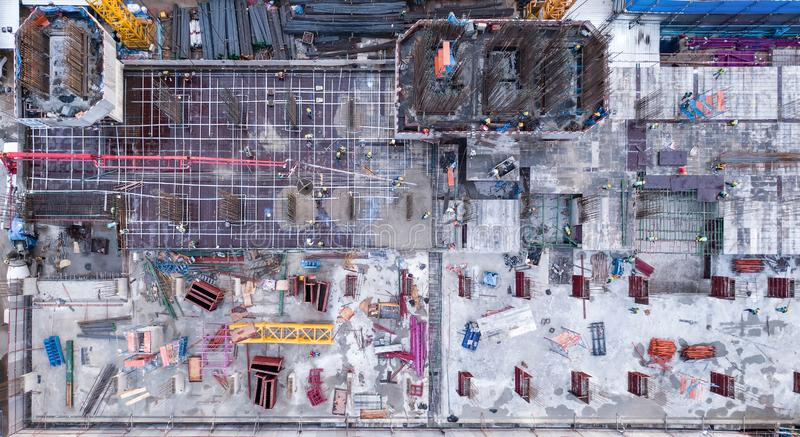 Aerial view of busy industrial construction site workers with cranes working. Top view of development high rise architecture. Building at noon stock image