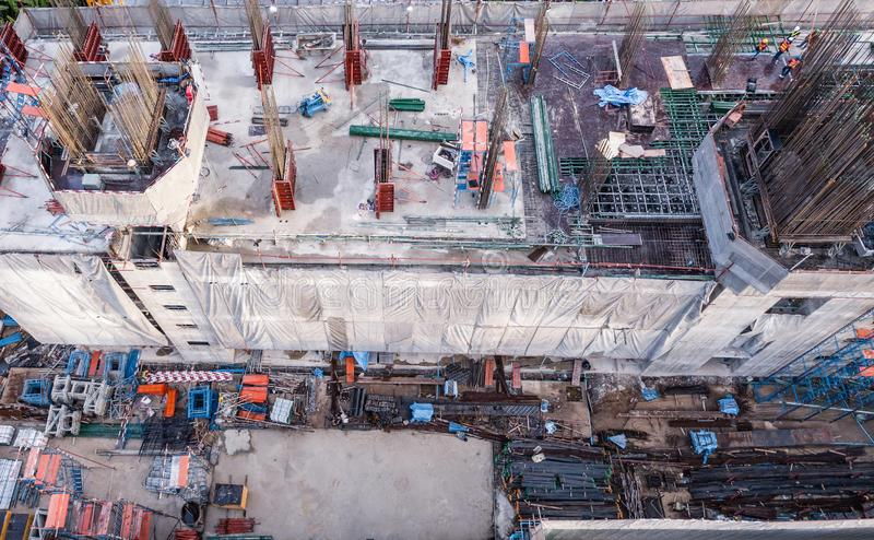 Aerial view of busy industrial construction site workers with cranes working. Top view of development high rise architecture. Building at noon stock images
