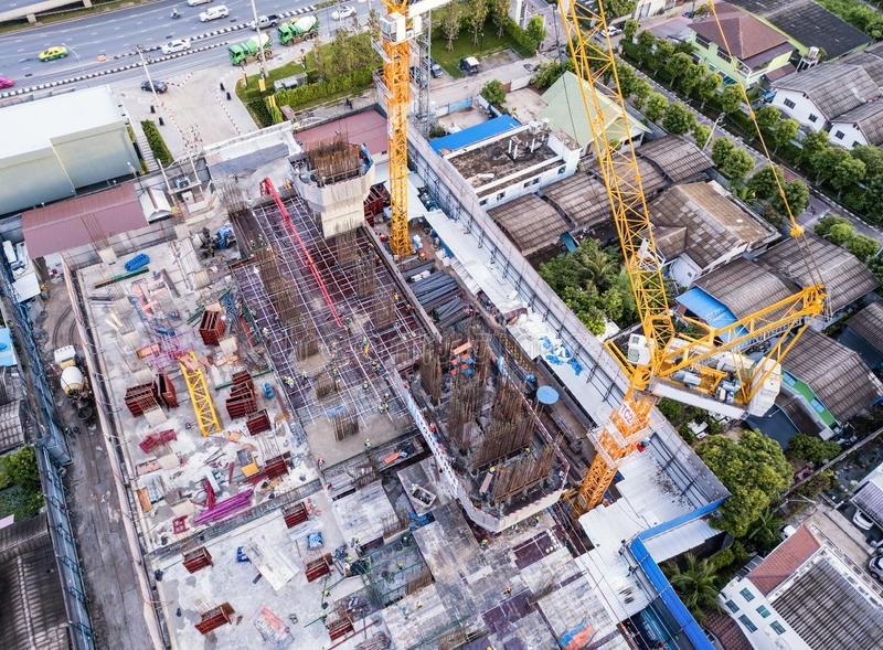 Aerial view of busy industrial construction site workers with cranes working. Top view of development high rise architecture. Building at noon stock photos