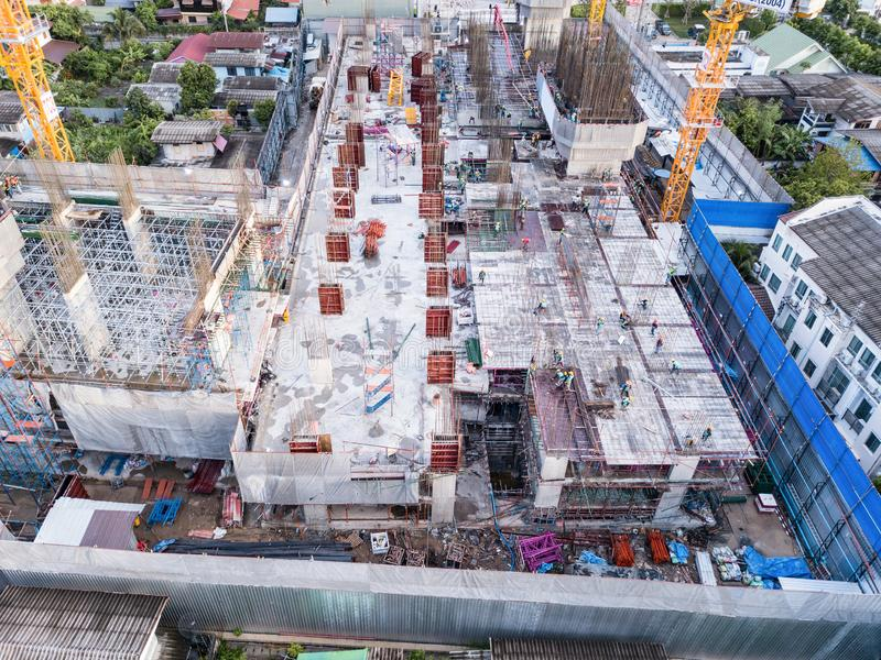 Aerial view of busy industrial construction site workers with cranes working. Top view of development high rise architecture. Building at noon royalty free stock photo