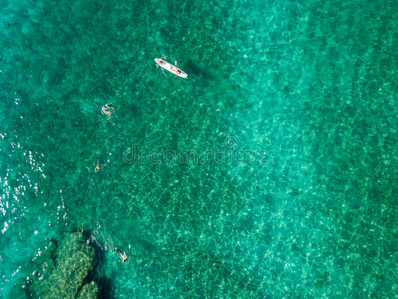 Aerial view of a canoe in the water floating on a transparent sea. Bathers at sea. Zambrone, Calabria, Italy. Diving relaxation and summer vacations. Italian royalty free stock image
